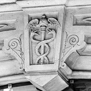 Detalle del relieve de un caduceo de Hermes en la entrada de un edificio de Barcelona.