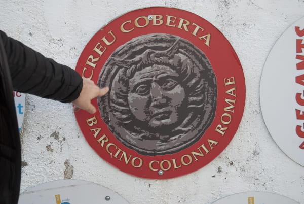 El distintivo de las jornadas de romanas de Barcelona organizadas en Creu Coberta contiene a Medusa fusionada con Hermes