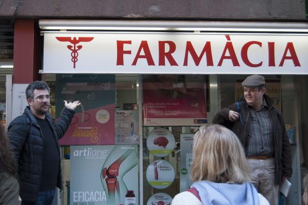 Albert Muñoz y Xavi Soro frente al del letrero de una farmacia con un caduceo de Hermes